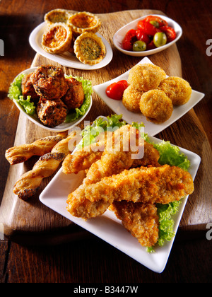 Party Food - from front - Chicken goujons, breaded cheese, onion bhajis, mini quicehe and sunblushed tomatoes and - Stock Photo