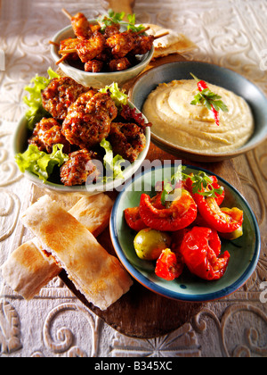 BBQ Party Food - From Front - Sun Blushed Tomatoes, Lamb Kofta, Houmous, Mini Marinated chicken kebabs with pitta - Stock Photo