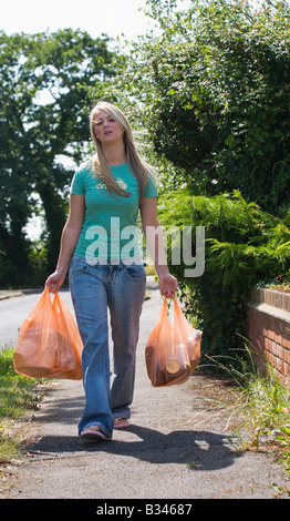 A young woman carrying heavy bags of shopping. UK  Walking home from the shops. - Stock Photo