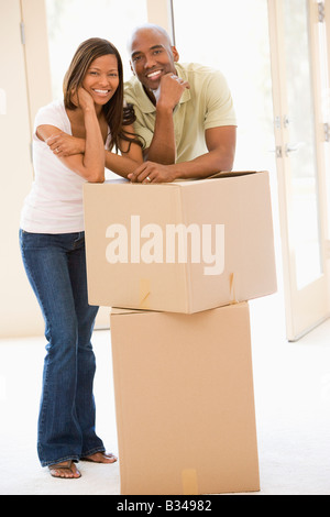 Couple with boxes in new home smiling - Stock Photo