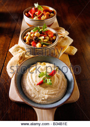 Party Food - From Front - Houmous, chick pea salad, marinated Mediterranean roast peppers - Stock Photo