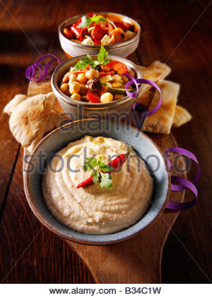 Party Food - From Front - Houmous, [chick pea] salad, marinated Mediterranean roast peppers - Stock Photo