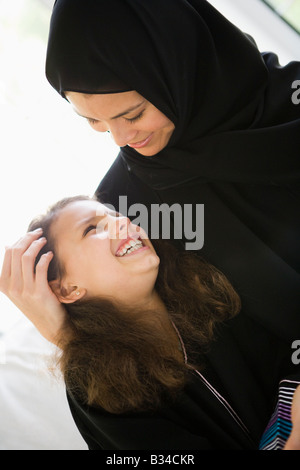 Mother and daughter in living room smiling (high key/selective focus) - Stock Photo