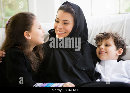 Mother and daughter sitting in living room smiling (high key/selective focus) - Stock Photo