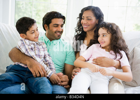 Family in living room sitting on sofa smiling (high key) - Stock Photo