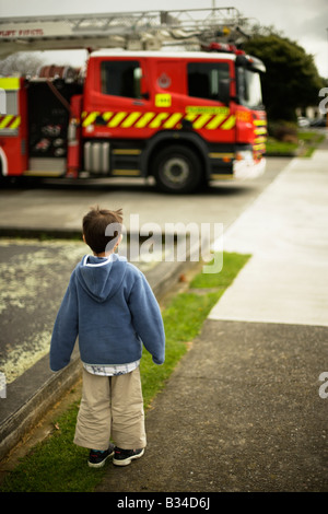Six year old boy looks at fire engine outside fire station in Palmerston North New Zealand - Stock Photo