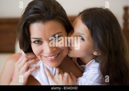 Young girl kissing smiling woman on cheek in bedroom (selective focus) - Stock Photo