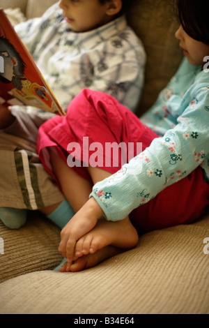 Boy aged six reads a story to his little sister aged five - Stock Photo
