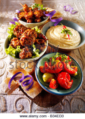 Party Food - From Front - Sun Blushed Tomatoes, Lamb Kofta, Houmous, Mini Marinated chicken kebabs with pitta bread - Stock Photo