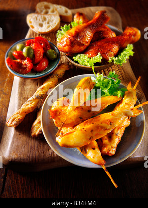party food - From Front - Marinated chicken skewers, Marinaded chicken drum sticks and sun blushed tomatoes. - Stock Photo