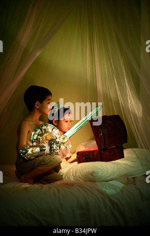 The magical treasure chest Five year old girl and six year old boy at play Brother and sister mixed race - Stock Photo