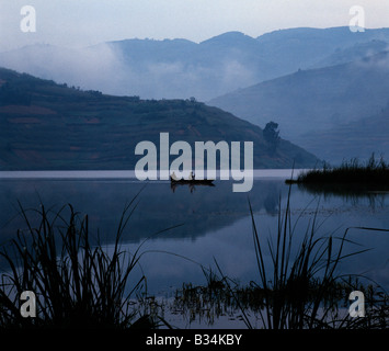 Uganda, Kabale, Lake Bunyonyi. Two men in a dugout canoe paddle across Lake Bunyonyi at twilight.Lake Bunyonyi lies - Stock Photo