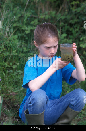 little girl in countryside looking at tadpoles in a jar - Stock Photo