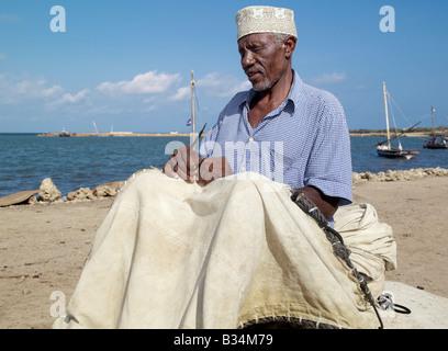 Kenya. A fisherman repairs the sail of his wooden sailing boat, known as mashua, along the waterfront of Kisingitini, - Stock Photo