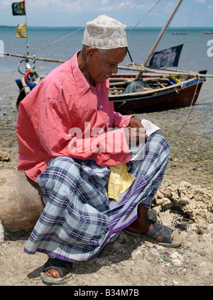 Kenya, Kisingitini, Pate Island. A man embroiders a Swahili hat along the waterfront at Kisingitini, a natural harbour - Stock Photo