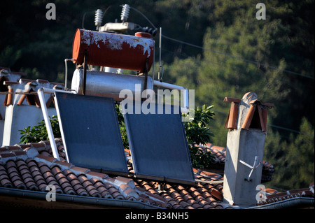 solar heating panels and water storage tank on Turkish house roof Akyaka Turkey - Stock Photo