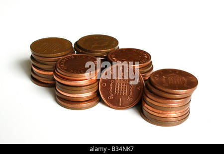 Piles of penny copper coins, with 1p  ( one pence ) standing.  ( Sterling ) - Stock Photo