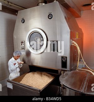 Quality control worker examining tablets in a pharmaceutical manufacturing plant - Stock Photo