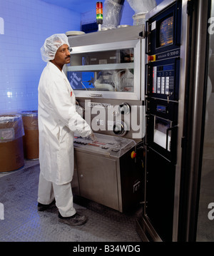 Worker operating machinery used to produce tablets in a pharmaceutical manufacturing plant - Stock Photo