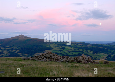 Sunset view of the Sugarloaf in the Black Mountains of South Wales with a moon rising above Abergavenny - Stock Photo