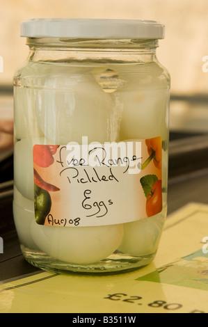 jar of organic pickled free range eggs aberystwyth farmers market wales UK, handwritten label - Stock Photo