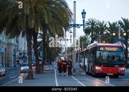 SPAIN Barcelona Woman walk down sidewalk under palm trees public bus on street near Las Ramblas - Stock Photo