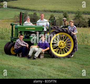 Farm equipment repairman and his family pose with an antique John Deere tractor. - Stock Photo