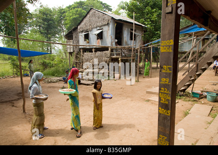 Young Vietnamese girls trading their wares in a floating village in the Red River Delta, Vietnam - Stock Photo