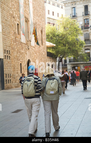 SPAIN Barcelona Tourist couple with backpacks walk down side street near Cathedral dressed khaki clothing - Stock Photo