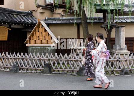 Two women wearing summer yukata robes passing by the entrance to the old red-light district of Shimbara in Kyoto