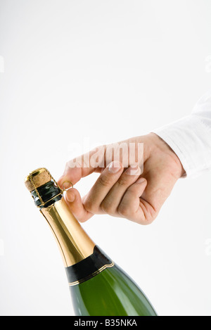 Hand opening champagne bottle - Stock Photo