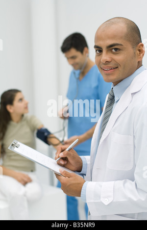 Doctor writing on clipboard, smiling at camera, nurse measuring patient's blood pressure in background - Stock Photo
