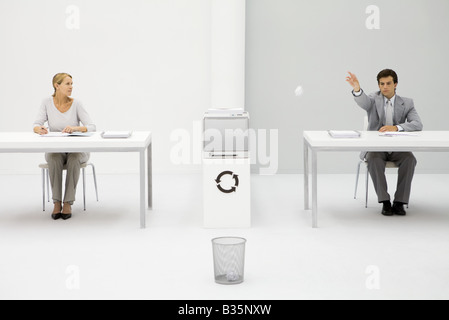 Male office worker throwing paper ball into trash can, female colleague watching - Stock Photo