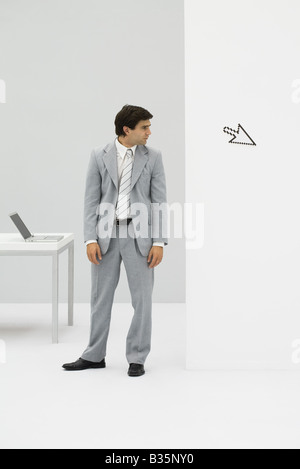 Businessman standing in office, looking at computer cursor pointing away - Stock Photo