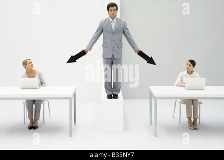 Businessman standing between two female employees, pointing arrows at each of them - Stock Photo