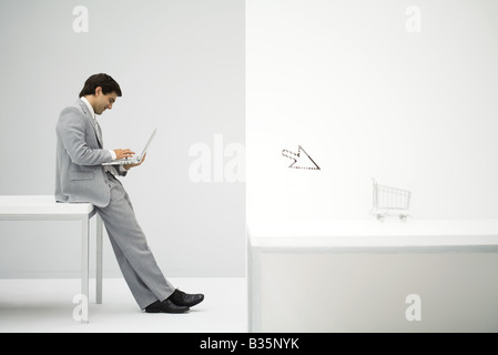 Businessman sitting on desk, shopping online, shopping cart and cursor in foreground - Stock Photo
