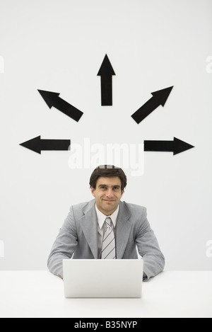 Businessman sitting with laptop, smiling, arrows pointing several directions above his head - Stock Photo