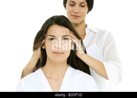 Woman receiving head massage, looking at camera - Stock Photo