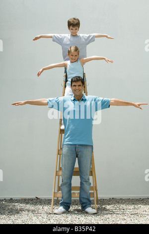 Boy and girl standing on ladder with arms in the air, father standing on the ground, all smiling at camera - Stock Photo