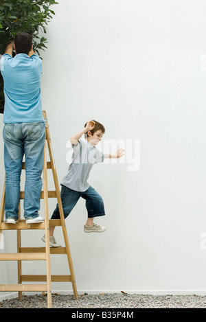 Father and son standing on ladder, boy leaping off - Stock Photo