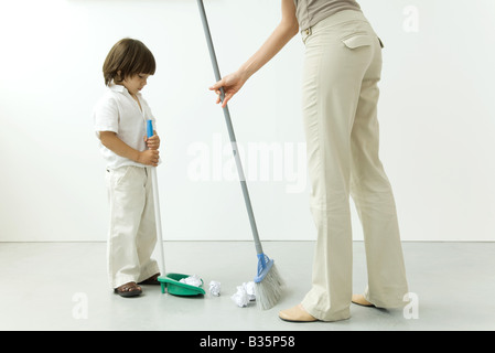 Little boy helping his mother sweep the floor, cropped view - Stock Photo