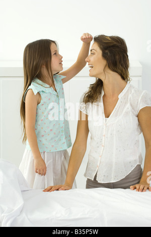 Little girl standing beside kneeling mother, comparing height with her hand - Stock Photo