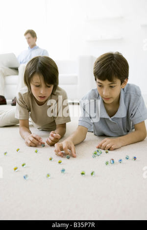 Boys lying on the floor playing with marbles, father sitting on sofa with laptop in background - Stock Photo