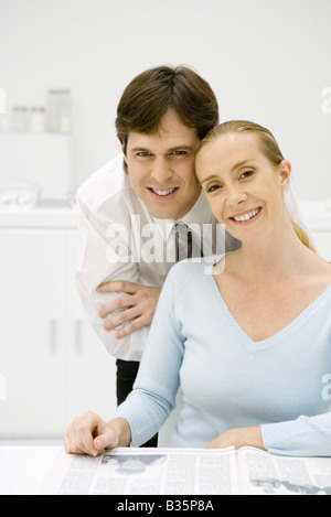 Couple smiling at camera together, woman sitting, man leaning over her shoulder - Stock Photo