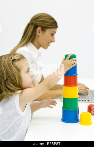 Young girl stacking multi-colored cylinders, young woman using laptop in background - Stock Photo