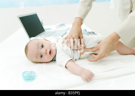 Mother changing baby's diaper on desk, laptop computer in background, cropped view - Stock Photo