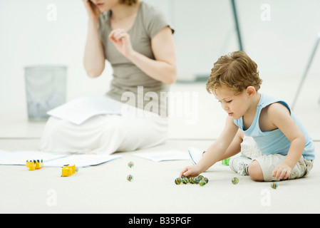 Little boy sitting on the ground, playing marbles, mother surrounded by paperwork in background - Stock Photo
