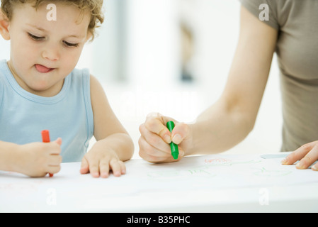 Mother and son coloring with crayons together, boy sticking tongue out, cropped view - Stock Photo
