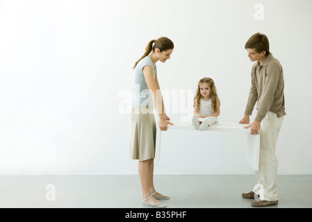 Young couple carrying table with daughter sitting on it - Stock Photo
