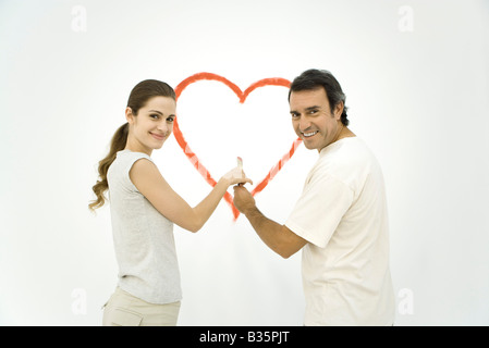 Couple standing in front of heart painted on wall, both holding onto the same paintbrush - Stock Photo